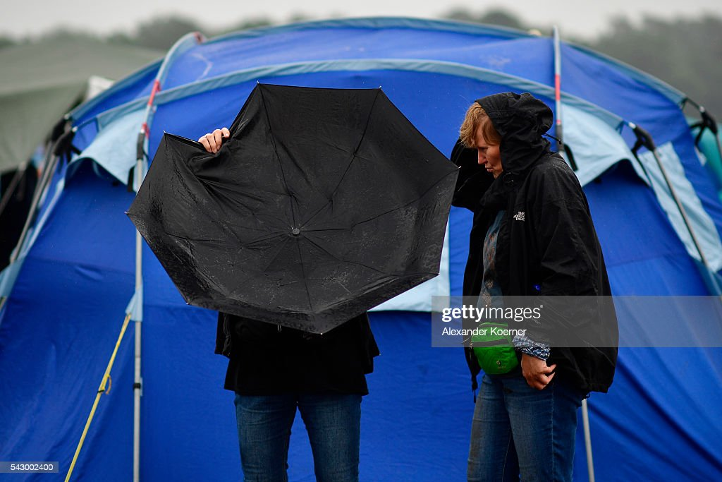 Two visitors check their umbrella during heavy rain at the muddy camping compound at the Hurricane Festival compound on June 25, 2016 in Scheessel, Germany. The Hurricane Festival was evacuated yesterday and was delayed today for the late evening, following heavy rain and thunderstorm alerts. The rain and thunderstorm have hit the festival during the night and day, causing damage to tents and flooded the festival site, only 7 concerts can be played on two stages today. The Hurricane Festival celebrates this year its 25th anniversary. 75.000 music fans have visited the Festival, but some thousands have already left the compound due to the current situation.
