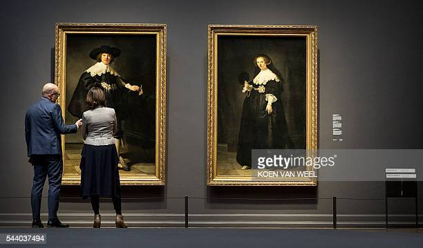 Two visitors look at Marten and Oopjen two Rembrandt portraits of a wedding couple jointly bought by the Netherlands and France and that are...
