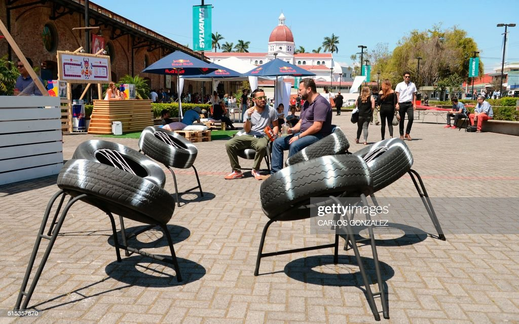 Two visitors sit on tyre seats during the International Design Festival (FID) in San Jose, Costa Rica, on March 10, 2016. Some hip designers in architecture, photography and even discreet sex toys got to strut their stuff in a three-day eclectic design showcase in Costa Rica.