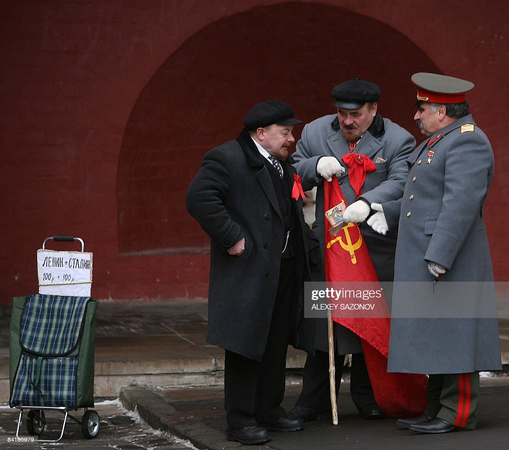 Two Vladimir Lenin and a Josef Stalin lookalike speak as they stand near a bag with a hand ade price list 'Lenin Stalin = 100 rubles 100 rubles' near...