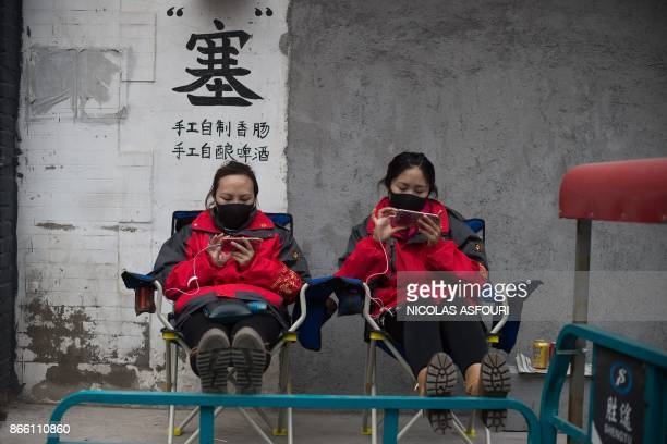 Two volunteers for security procedures watch Chinese President Xi Jinping attending the Communist Party of China's new Politburo Standing Committee...