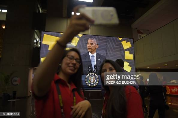 TOPSHOT Two volunteers take a selfie in front of a screen broadcasting US President Barack Obama's press conference after attending the AsiaPacific...
