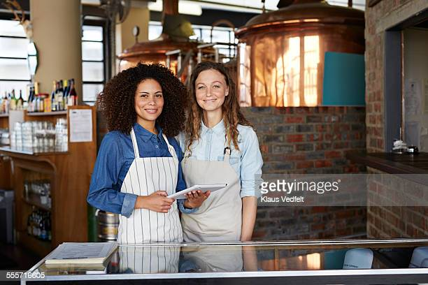 Two waiters holding tablet at restaurant