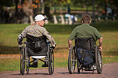 Two war veterans in wheelchairs in a park