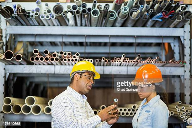 Two warehouse workers looking at copper pipe