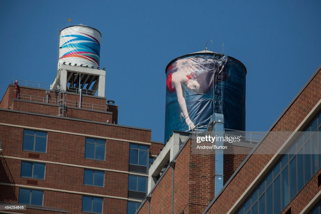 Two water tanks, reimagined and wrapped as artistic canvases by artists Laurie Simmons (R) and Odili Donald Odita (L) for The Water Tank Project, are seen on August 27, 2014 in the Chelsea neighorhood of New York City. The Water Tank Project will wrap over 100 water tanks around New York City with art by both new and established artists through the end of October 2014. The goal of the project is to raise awareness about water usage and the environment.