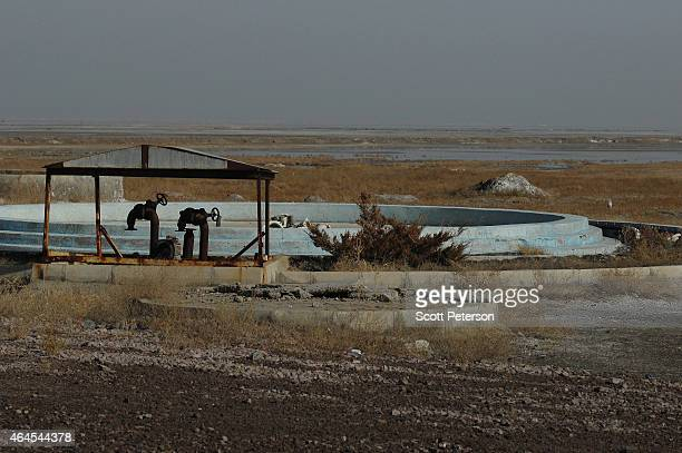 Two water valves stand empty at a resort along the former lakebed of Iran's shrinking Lake Urmieh is presenting a risk of salt storms and future...