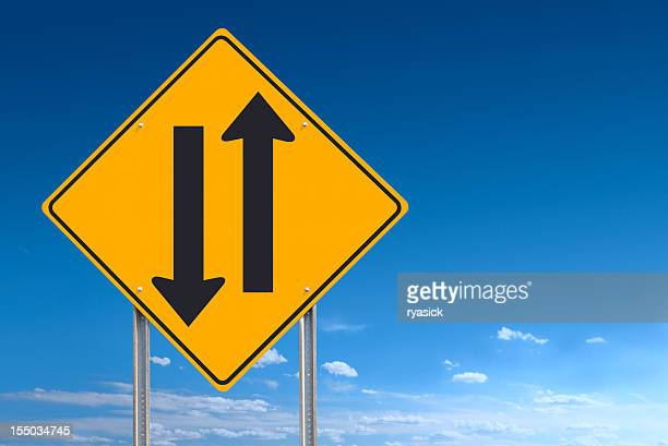 Two Way Road Sign Showing Opposing Directions on Blue Sky