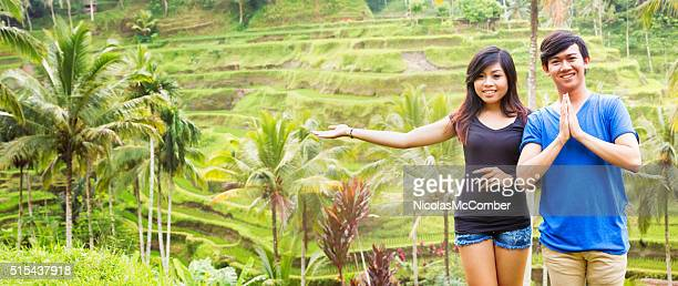 Two welcoming young Indonesian friends show rice paddy panorama