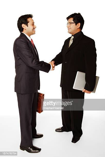 Two well-dressed Indian business men shaking hands (isolated on white)