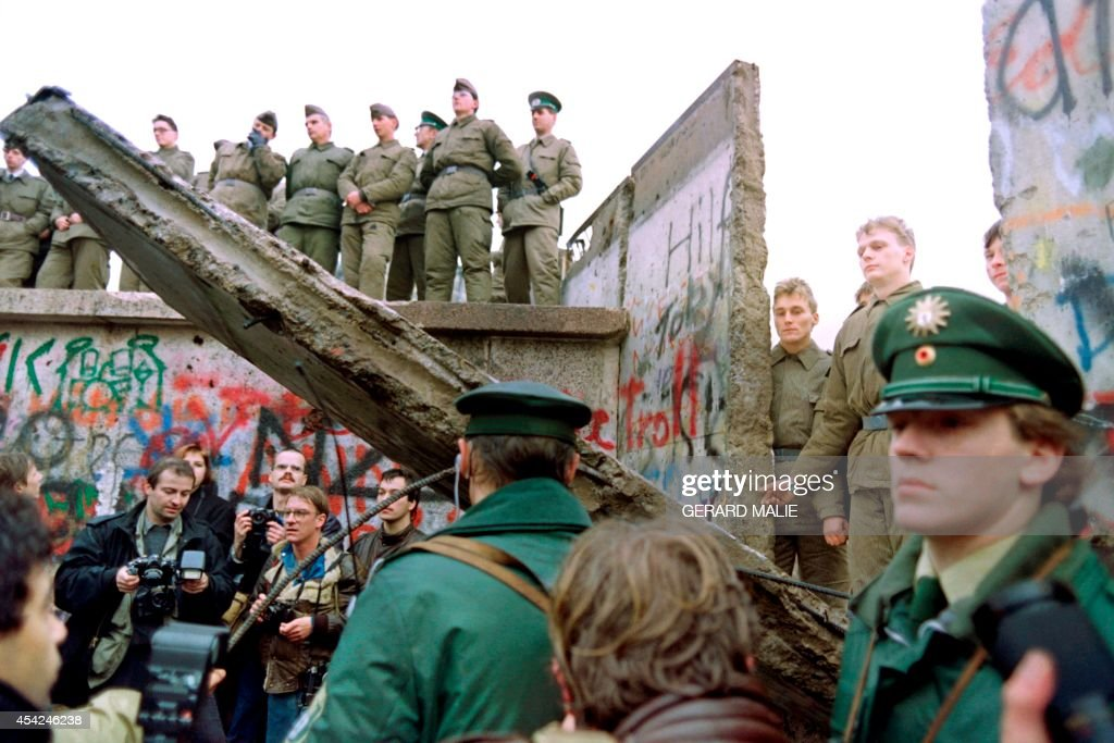 Two West German policemen prevent people from approaching as East German Vopos stand on and near a fallen portion of the Berlin Wall 11 November 1989. Two days before, Gunter Schabowski, the East Berlin Communist party boss, declared that starting from midnight, East Germans would be free to leave the country, without permission, at any point along the border, including the crossing-points through the Wall in Berlin. The Berlin concrete wall was built by the East German government in August 1961 to seal off East Berlin from the part of the city occupied by the three main Western powers to prevent mass illegal immigration to the West. According to the 'August 13 Association' which specialises in the history of the Berlin Wall, at least 938 people - 255 in Berlin alone - died, shot by East German border guards, attempting to flee to West Berlin or West Germany.