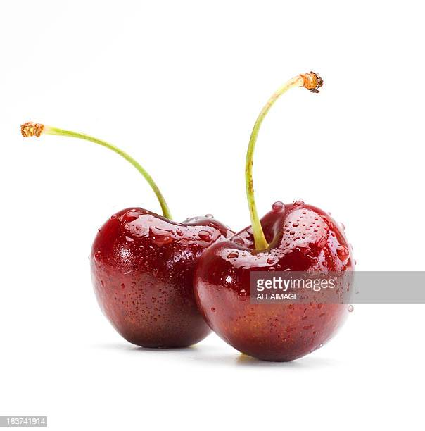 Two wet cherries on a white background