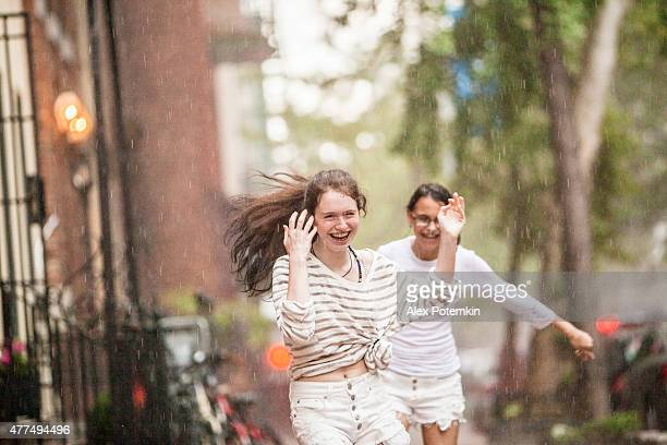 Two wet teenager girl, sisters, running under the summer rain