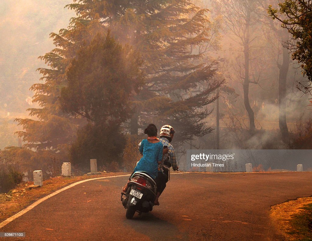 Two wheeler passing through the thick smoke due to the heavy forest fire at Godkhyakhal near Pauri, on May 1, 2016 in Uttarakhand, India. Two Indian Air Force (IAF) choppers began spraying water over the burning forests in Uttarakhand on Sunday morning. Major forest fires raged across Uttarakhand even as two Indian Air Force (IAF) choppers have begun spraying water to extinguish the flames. Presently, some 5,000 workers -- including 3,000 daily wagers -- are engaged in putting out the fire. More than 2300 hectares of forest have been gutted in the fire since it was first reported in February this year. Dry winters and soaring temperatures are blamed for the fire that has affected all 13 districts of the state.