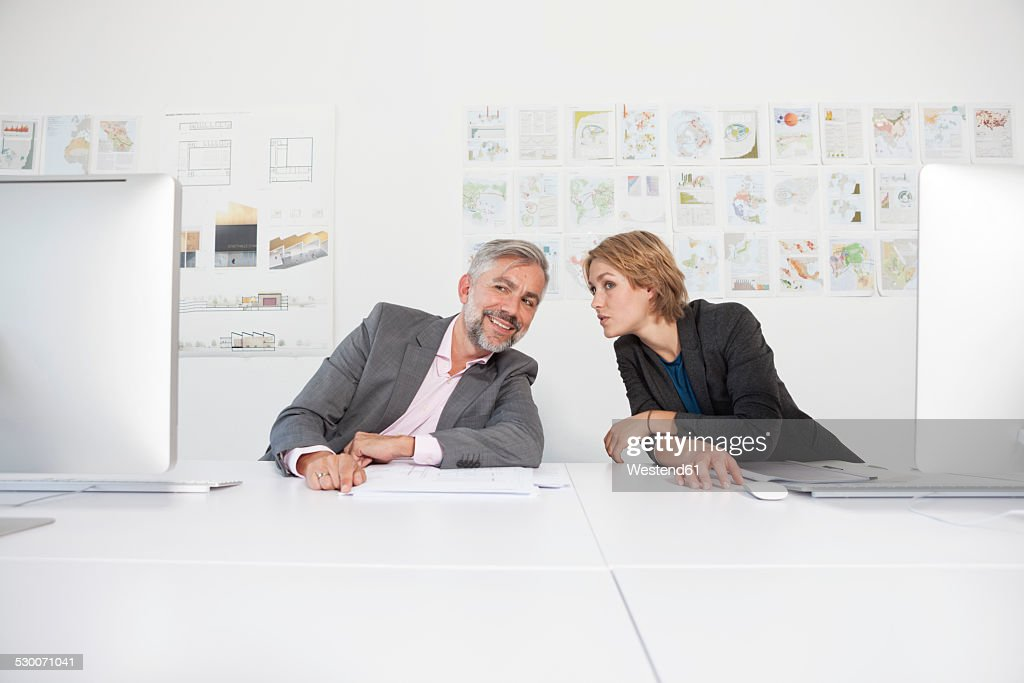 Two whispering colleagues at their desks in an office