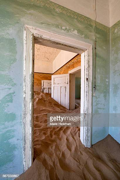 Two white doors stuck in sand in abandoned house