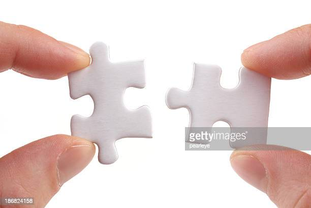 Two white jigsaw puzzle pieces being slotted together