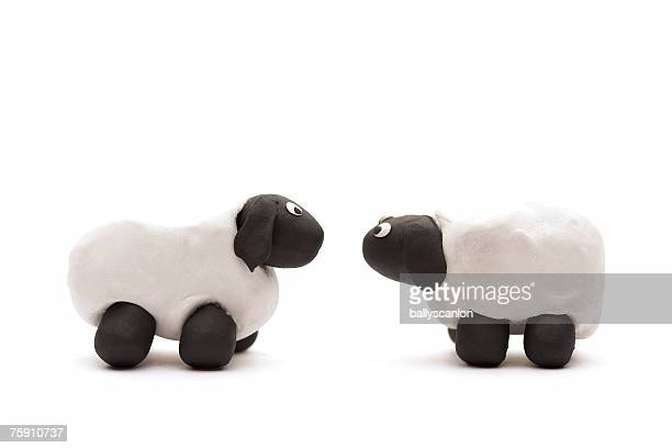 Two white sheep made of clay facing each other on white background