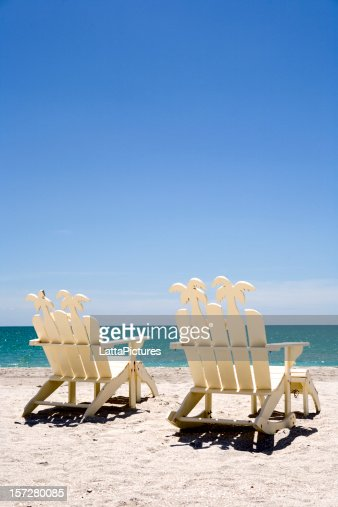 Two white wooden beach chairs on sand with ocean