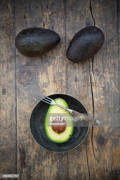 Two whole and a half avocado (Persea Americana) on wooden table