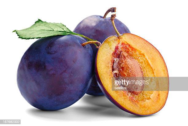 Two whole and one sliced plum with flesh and pit showing