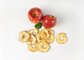 fresh red apples and dried apple rings on white background
