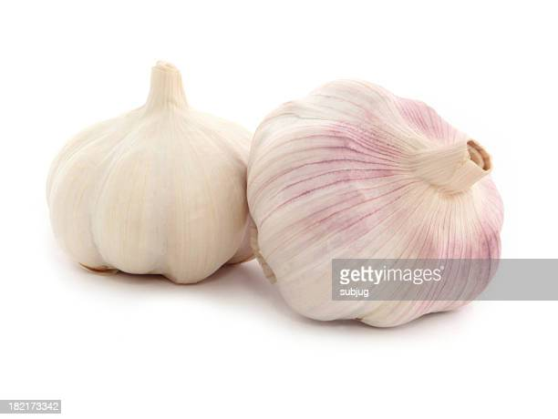 Two whole garlic bulbs one tinted purple on white background