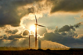 Two wind turbines and irrigating crop water gun or water spray at sunset in backlight against an orange colored dramatic cloudy sky and bright sun