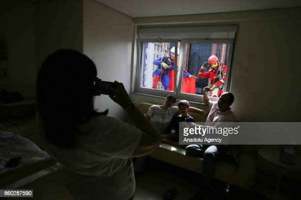 Two window washers dressed as Iron Man and Superman abseil the windows of a hospital specializing in cancer treatment as they pose for a photograph...