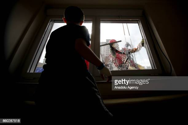 Two window washers dressed as Iron Man and Superman clean the windows of a hospital specializing in cancer treatment as they greet a child patient at...
