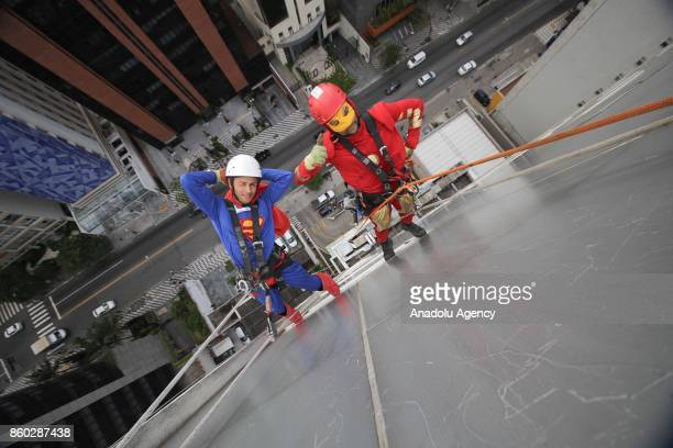 Two window washers dressed as Superman and Iron Man abseil the windows of a hospital specializing in cancer treatment as they pose for a photograph...