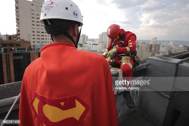 Two window washers dressed as Superman and Iron Man prepare to abseil the windows of a hospital specializing in cancer treatment at Angelica Avenue...