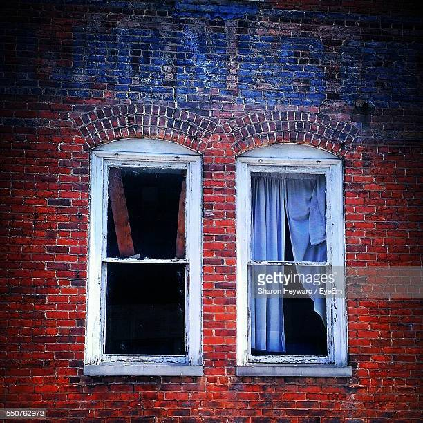 Two Windows On Red Brick Wall
