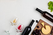 Two wine glasses with red and white wine,bottles of red wine and white wine, cheese on white background. Horizontal view from the top. Mock-up. Copy space. Flat lay