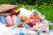 Two wine goblets, fresh strawberry, honey and wine are served for summer romantic picnicPicnic Basket with apples and bread. Family disfocused. Copy space.