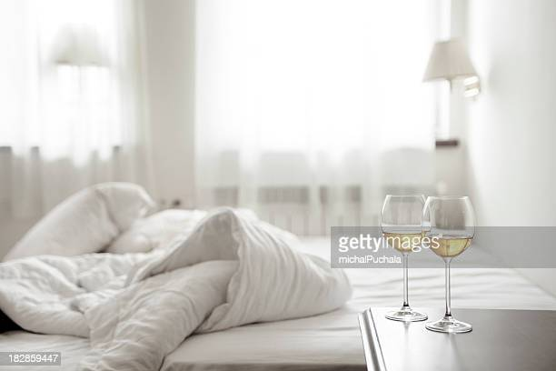 Two wineglasses and wrinkled bedding
