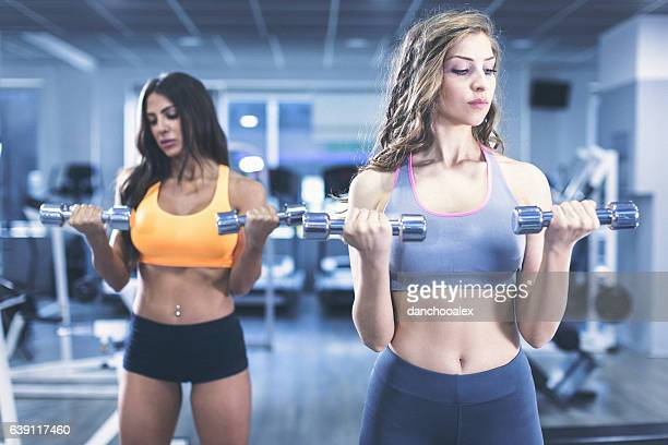 Two woman at gym lifting weights