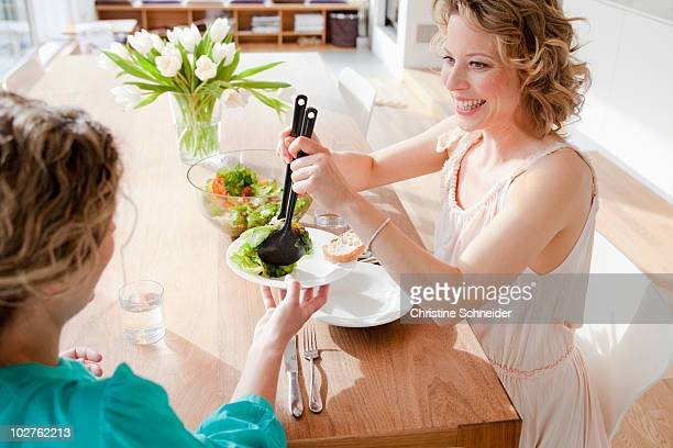 Two woman at table with mixed salad