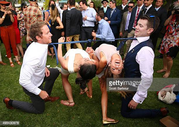 Two woman bends backwards between two racegoers who have their ties tied together as racegoers play a game of Limbo following 2015 Melbourne Cup Day...