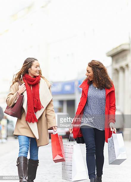 Two woman chatting whilst walking in street.