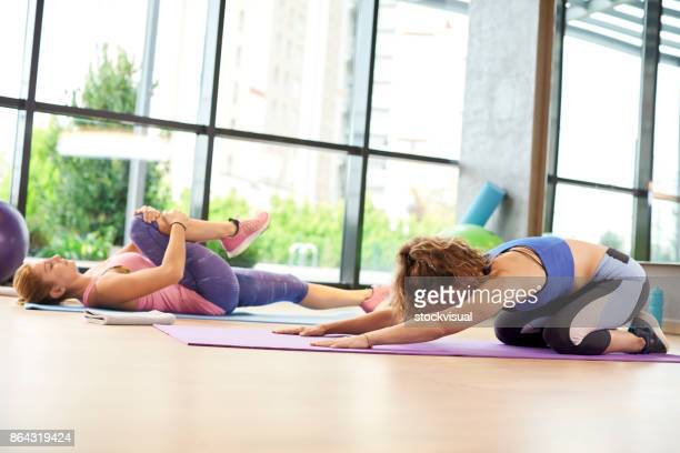 Two woman doing streching in a class in a gym