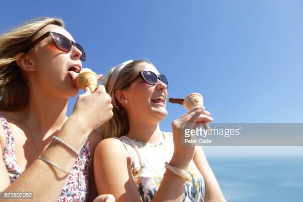 Two woman eating ice cream sat on car by the sea