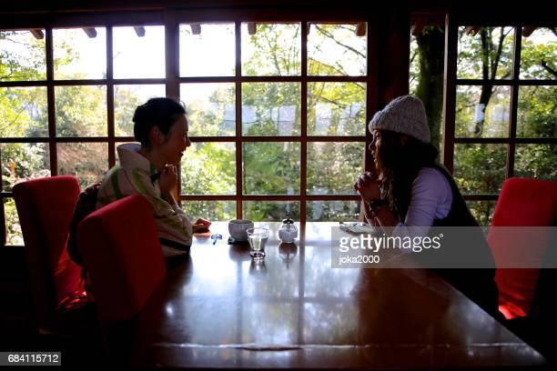 Two woman enjoying talk in cafe