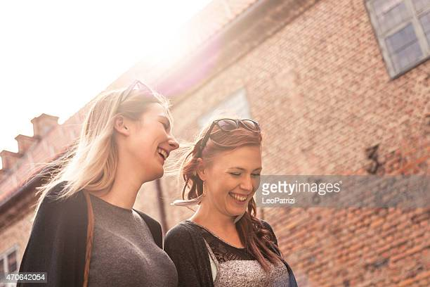 Two woman friends walking in the city enjoying their time
