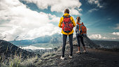 Two hikers stand on the top of a mountain and enjoy valley view