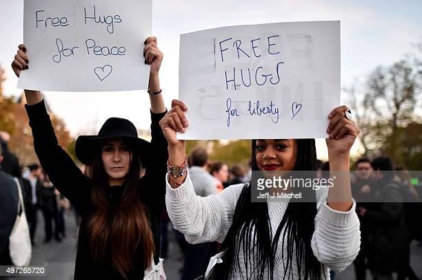 Two woman hold signs offering free hugs as people gather at Place de la Republique as France observes three days of national mourning for the victims...