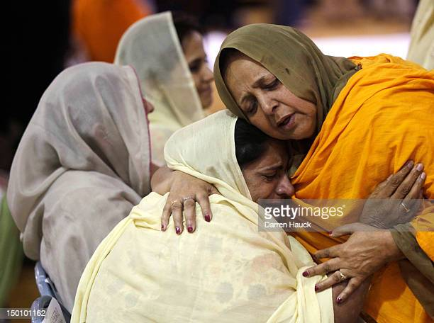 Two woman hug as community members pay respects to the six victims in the mass shooting at the Sikh Temple of Wisconsin at the Oak Creek High School...
