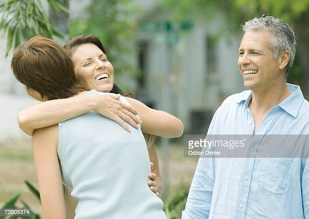 Two woman hugging while man watches