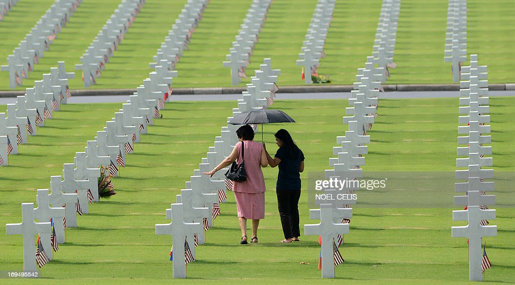 Two woman look at the graves of soldiers who fell during World War II, during services to mark US Memorial Day at the Manila American Cemetery in Fort Bonifacio in Manila on May 26, 2013. At least 17,000 graves are in the park that pays tribute to US and Philippines soldiers that fought side-by-side during World War II. The US marks Memorial Day on May 27.