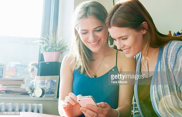 two woman looking at mobile phone